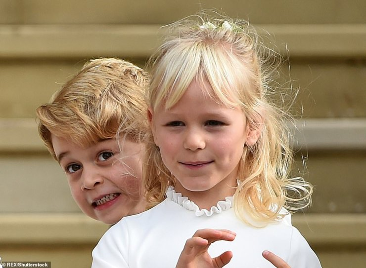 George the joker! The young Prince was pictured playing tricks on his cousin Isla Phillips at St George Chapel, in Windsor, on the day of Princess Eugenie's wedding on October 12 2018