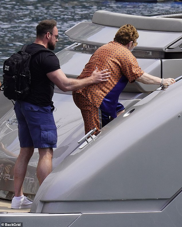 Helping hand: A man helped the singer climb the stairs of the boat, which appeared to be smaller than yachts he has used in the past