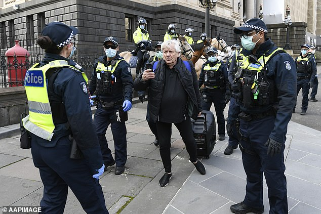 August 9, 2020: A man leaves after being questioned by police during an anti-lockdown protest in Melbourne