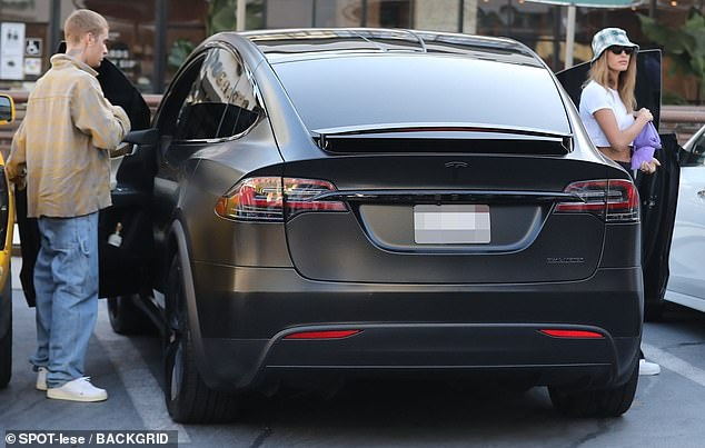 Ride in style: A-list couple were seen stepping out of a matte black Tesla