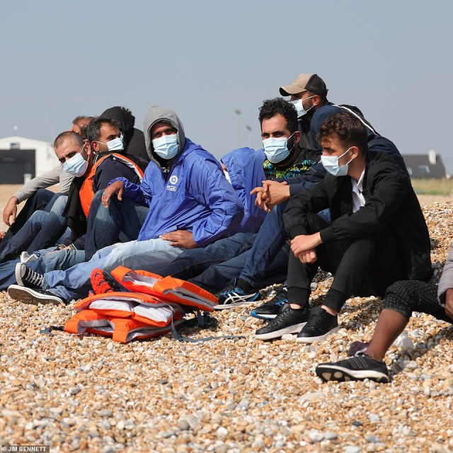 Migrants wearing masks sitting on the beach atDungeness in Kent after they are brought ashore