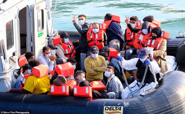 Up to 30 migrants are brought ashore by Border Force officials yesterday as the crisis in the Channel continues