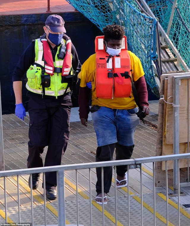 A migrant is seen being taken ashore by a Border Force official after their boat was intercepted in the Channel