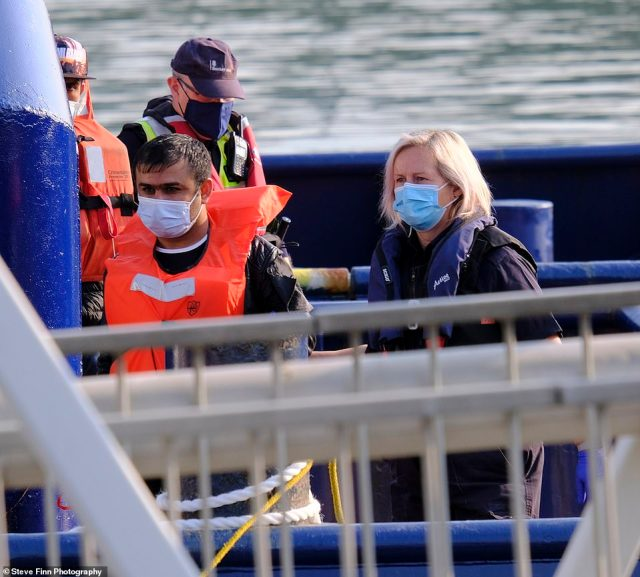 Migrants are seen being taken ashore by Border Force officials in Dover Marina, Kent yesterday