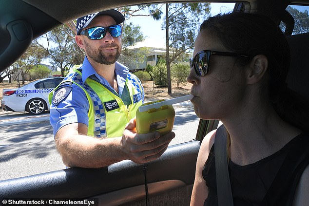 In Queensland, it is illegal for passengers to have an open bottle of alcohol in the car while it is en route.  Pictured: Australian traffic police officer uses breathalyzer on female driver