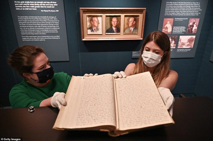 Royal Collection Trust creator Sally Goodsir makes adjustments to the display during a preview for Prince Philip: A Celebration, commemorating the life and work of the Duke of Edinburgh (pictured, the Midshipman's log book from 1940)
