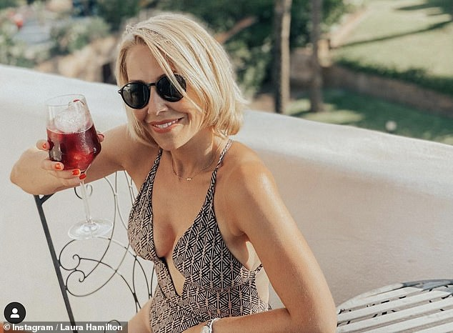 Sizzling: Laura Hamilton flaunted her sensational figure in a swimsuit as she sipped a tall glass of Sangria in an Instagram photo shared Wednesday