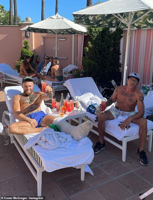Road to recovery: Conor McGregor put his feet up as he relaxed on a recliner while on vacation on Thursday, a week after sustaining a horror leg fracture during UFC 264