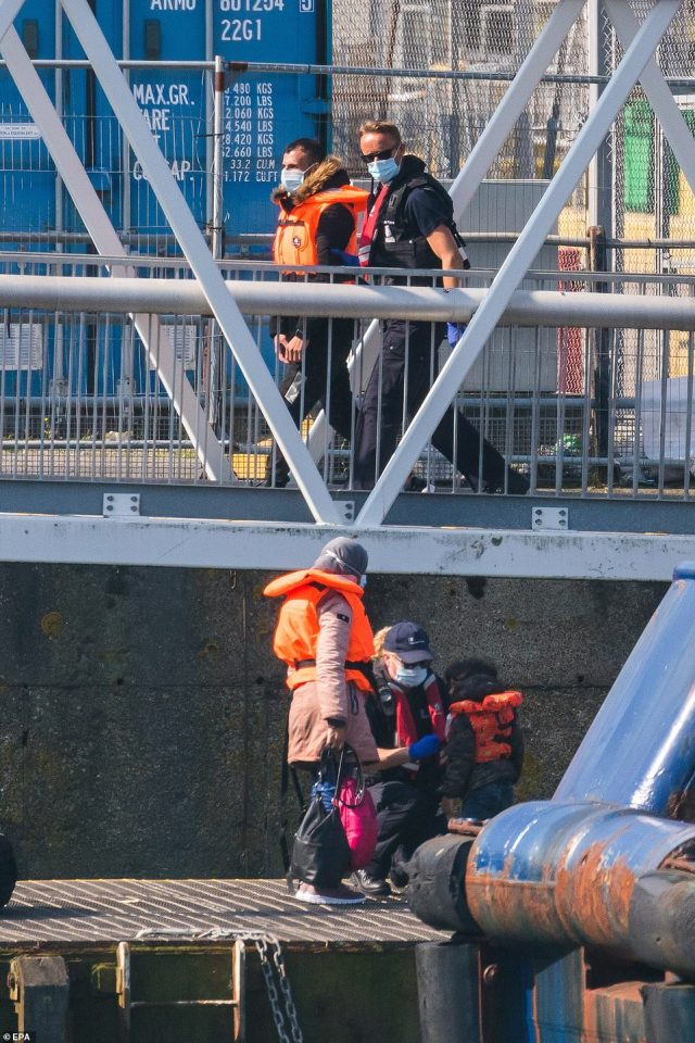 Border Force staff bring people onshore including children thought to be migrants found in the English Channel off the coast of Dover in Dover, Kent