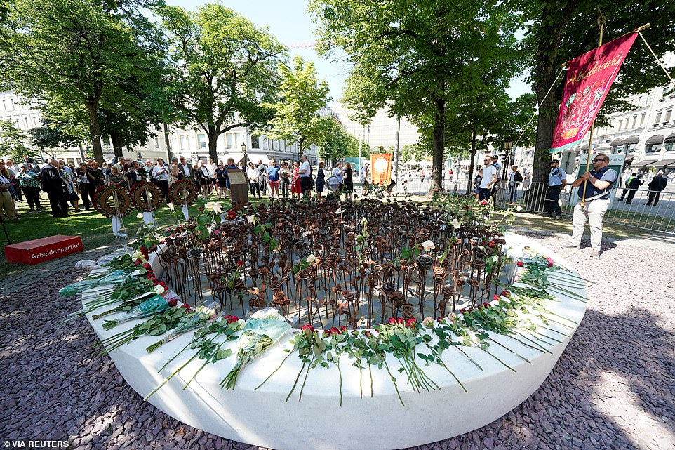 People gather next to a memorial outside the Oslo Cathedral today in a service to honour the 77 vicitms of the horrific attack in 2011