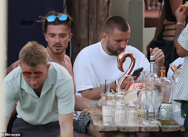 Casual: Jack opted to go topless as he sat beside a wooden table surrounded by drinks and friends