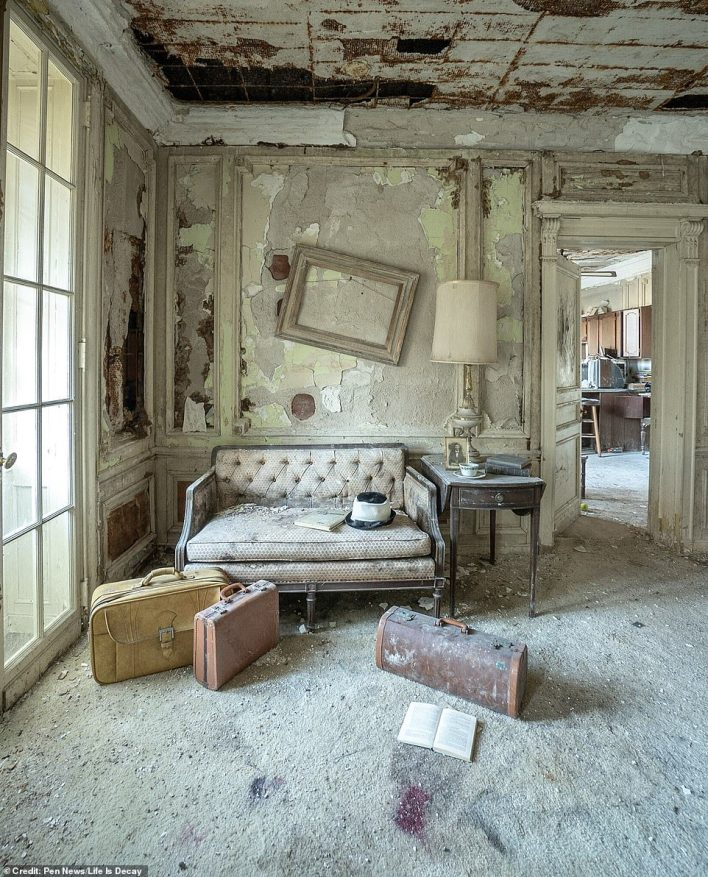 This room has clearly seen better days. Both the ceilings and walls have severe damage from where paint and wallpaper has fallen away. Against the wall, an old sofa is covered in dust
