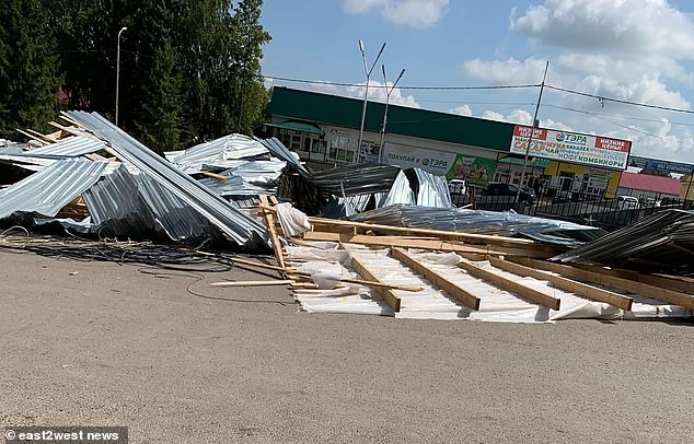 The remains of the roof can be seen in a heap on the ground where they fell on the girl after being blown away by the wind