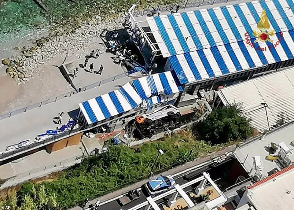 Pictured: An aerial view of the bus lying on its side at the bottom of a cliff after crashing through a guardrail, on the island of Capri, Italy, Thursday, July 22, 2021