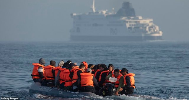 An inflatable craft carrying migrant men, women and children crosses the shipping lane in the English Channel today