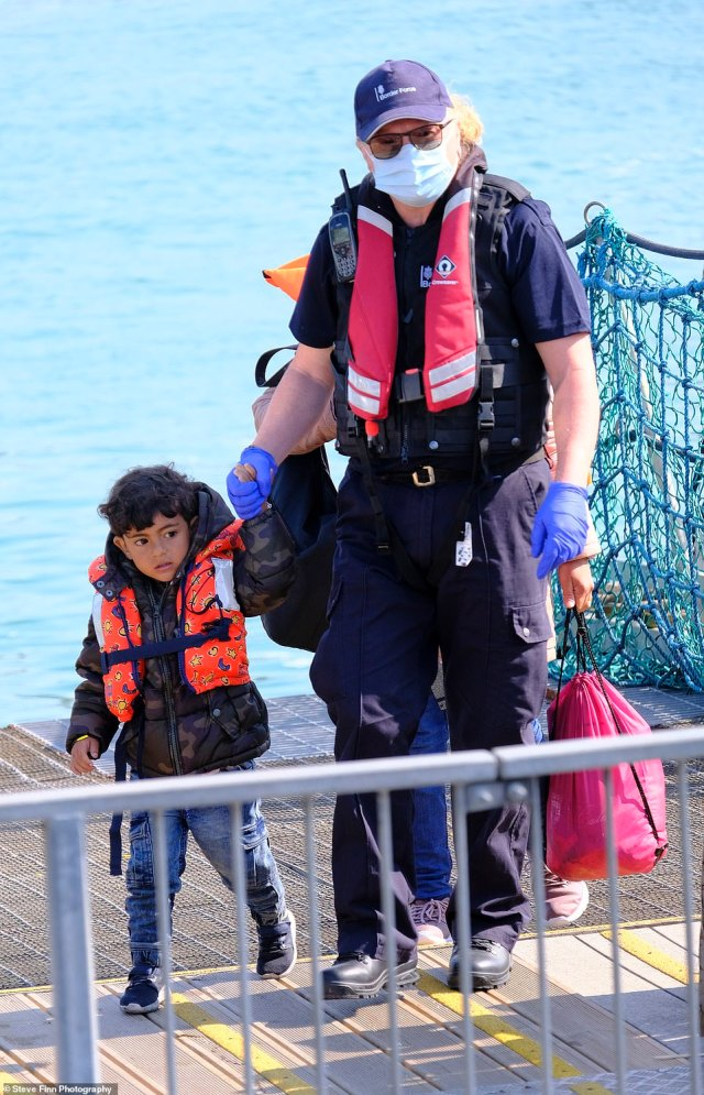 A little toddler was held by their hand as they were brought into Britain after landing on the dinghies this morning