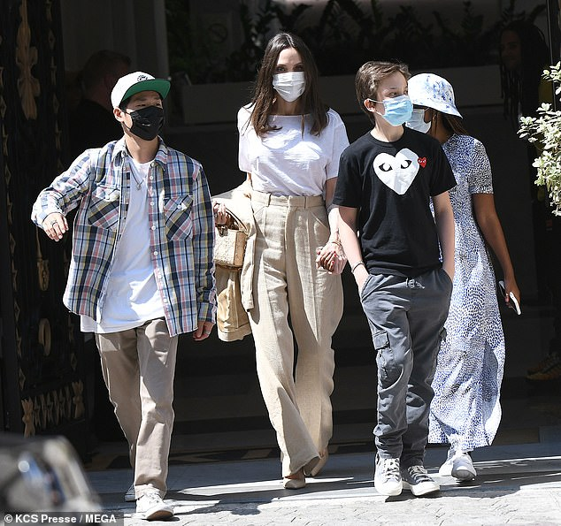 Angelina Jolie stylishly undresses in a white shirt and beige trousers as she steps outside with children Pax, 17, Zahara, 16, and Shiloh, 15, in Paris