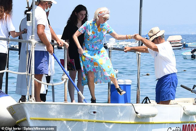 Slowly does it: Trudie held onto her pretty dress and was helped onto the boat by a man