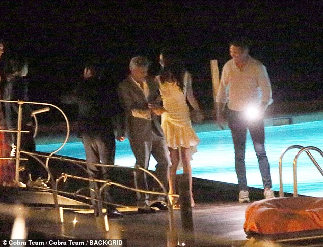 Here come the boys: George seemed in a good mood as he talked to Amal and his brother-in-law