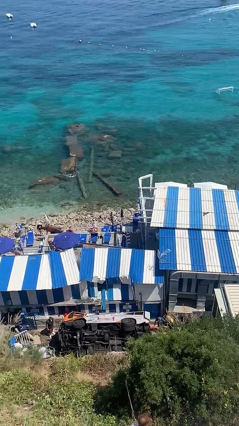 Pictured: The bus seen lying on its side after crashing down a cliff and onto a beach resort at the bottom on Thursday, with one person confirmed dead