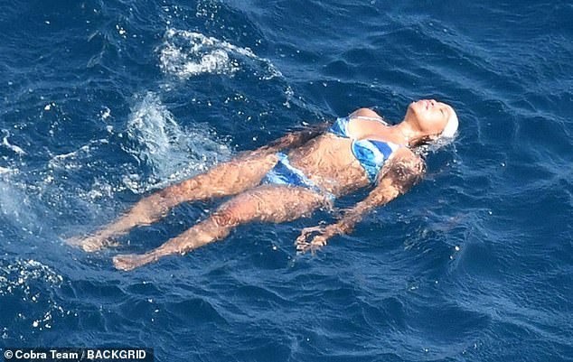 Relaxing: The director of One Night in Miami showed off her fit 5ft3in figure in a blue tie-dye underwire bikini