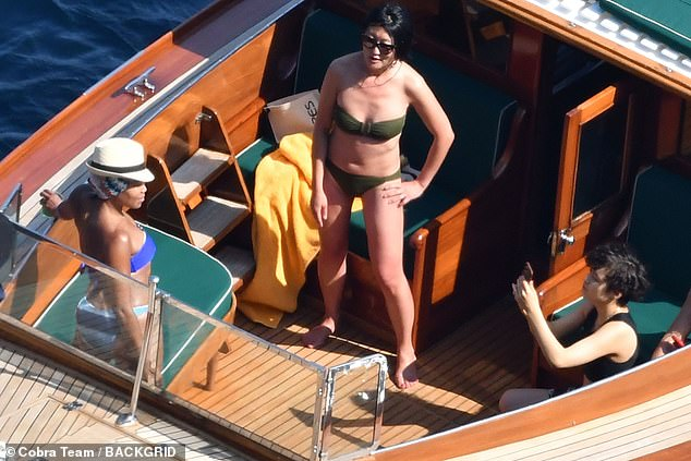 Pose!  Regina smiled as she posed for a photo on the boat by a friend (R) wearing a black crop top and shorts