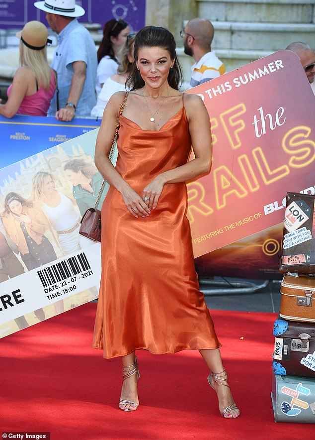 Chic:Faye Brookes looked sensational in an orange satin dress as she attended the Off The Rails premiere in London on Thursday