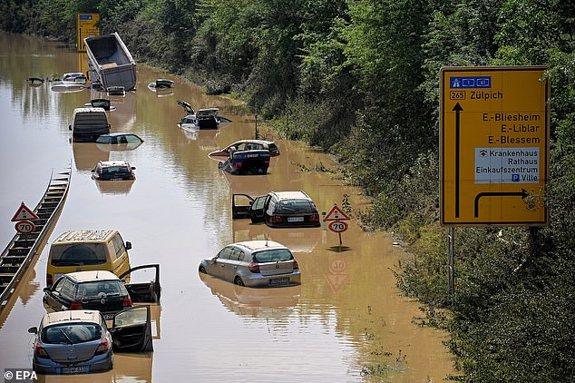 Wrecked cars and trucks are flooded on the B265 federal highway in Erftstadt, Germany