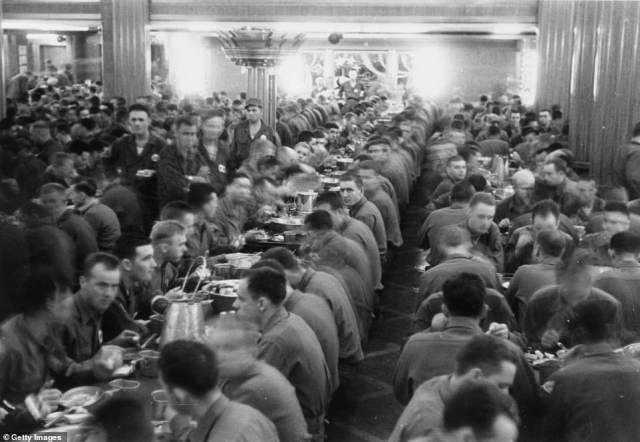 The luxury dining room of the Queen Mary served a mess hall for American soldiers, while the vessel carries out her duties as a troopship during World War II