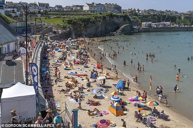 A busy Towan beach in Newquay, Cornwall, is pictured above as holidaymakers enjoy their summer holiday in the region today