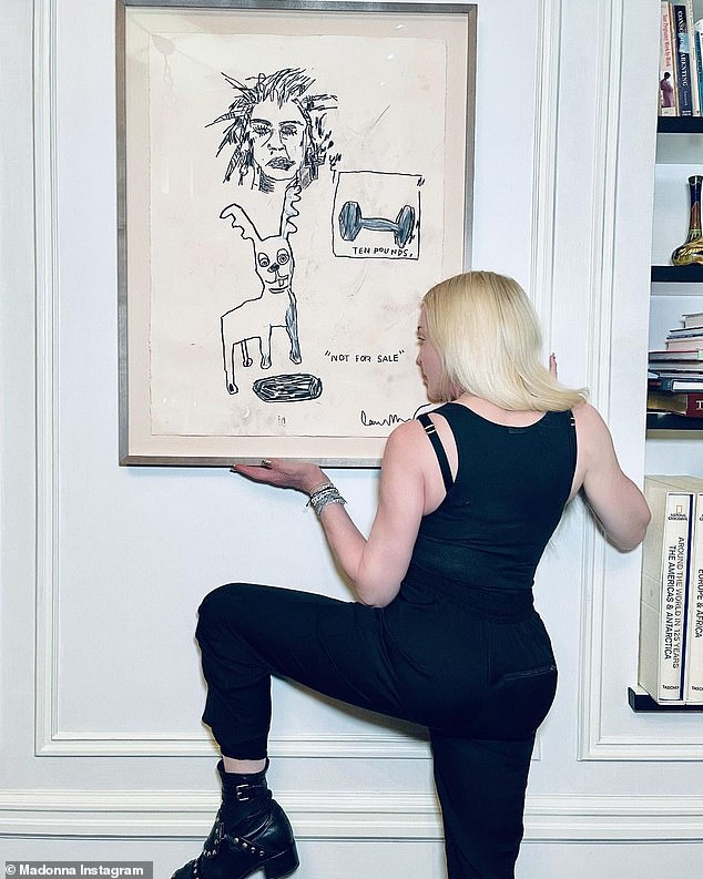 Showing respect:Madonna sat in front of the arresting piece of art and at one point took off her hat and faced away from the camera as she put her hand right under the frame