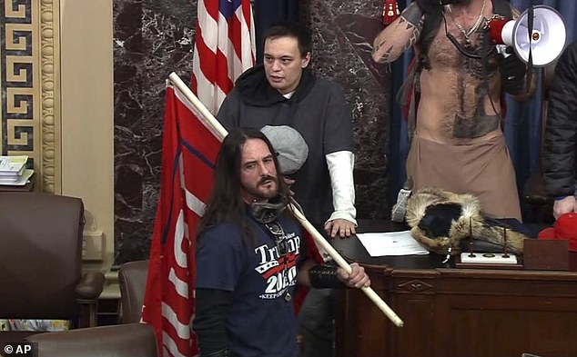 In this file image of the US Capitol Police video, Paul Allard Hodgkins, 38, of Tampa, Florida, stands front, in the pit on the floor of the US Senate on January 6.  Hodgkins was sentenced Monday to eight months in prison