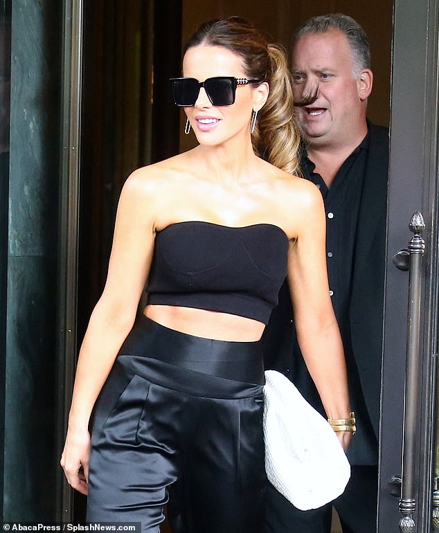 Red Hot: The Underworld actress, 47, showed off her washboard abs and toned frame in a tiny black bandeau top as she strolled