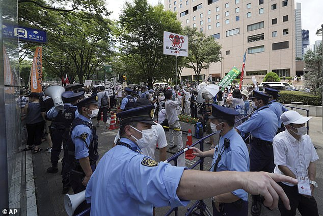 Police block angry protesters from accessing the torch relay event, amid widespread opposition to the Games in Japan