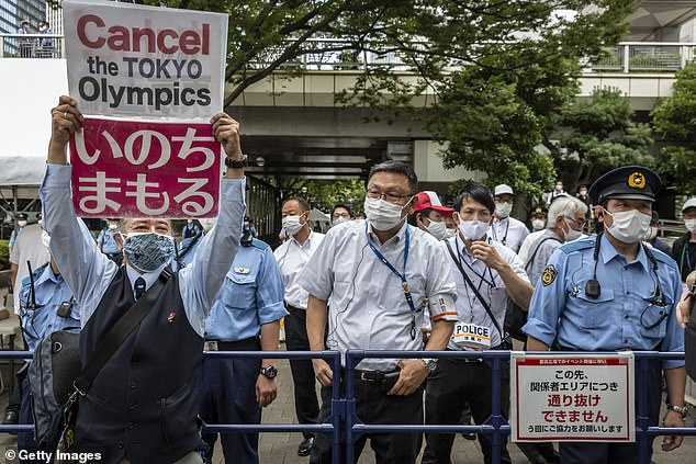Police block demonstrators from accessing an arena where the final stages of the Olympic torch relay are taking place before the opening ceremony