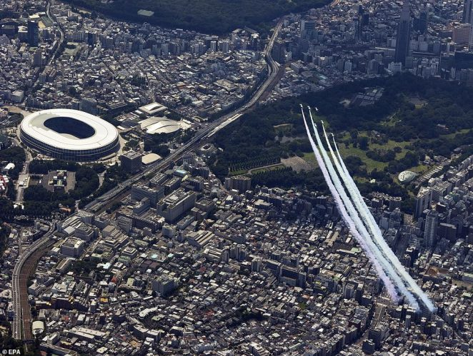 Japanese display team Blue Impulse take part in an aerial show over Tokyo's Olympic stadium ahead of the opening ceremony