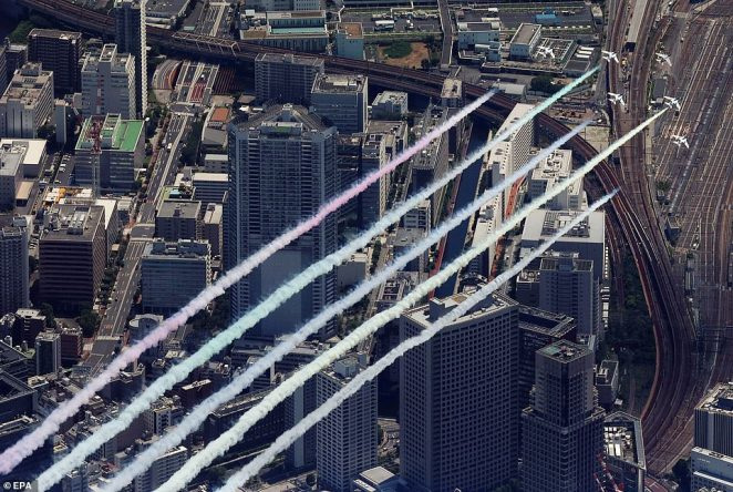 Blue Impulse display jets release coloured smoke over Tokyo hours before the main Opening Ceremony is due to take place