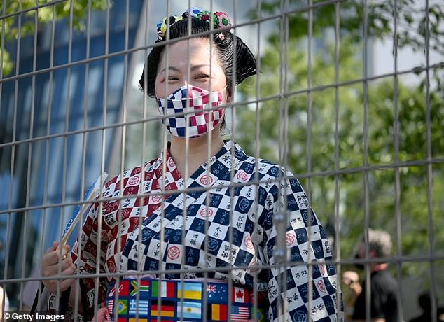 A woman in traditional clothing looks on from behind a fence prior to the Opening Ceremony of the Tokyo 2020 Olympic Games