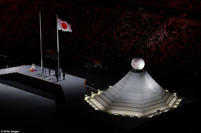 Japan raises its flag in the Olympic Stadium as the national anthem is sung during the opening ceremony