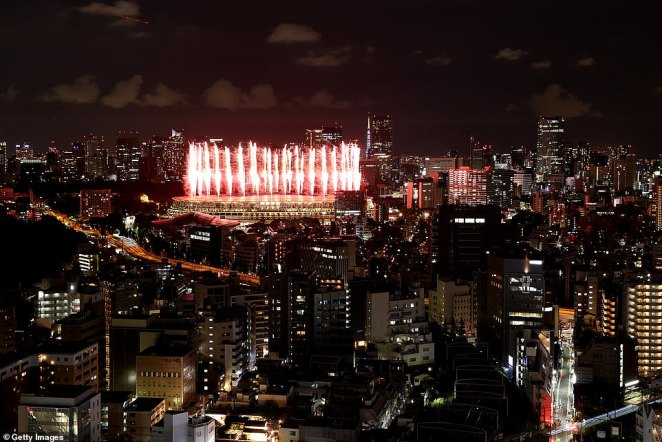 The main Olympic stadium in Tokyo is seen illuminated against the city skyline during the opening ceremony