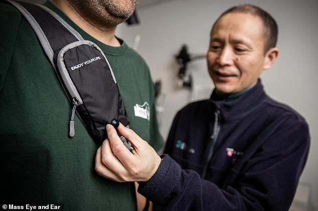 Gang Luo, PhD, displays the camera on the strap of wearable collision device. The camera is connected to a processing unit that captures images and analyses collision risk based on the relative movement of incoming and surrounding objects
