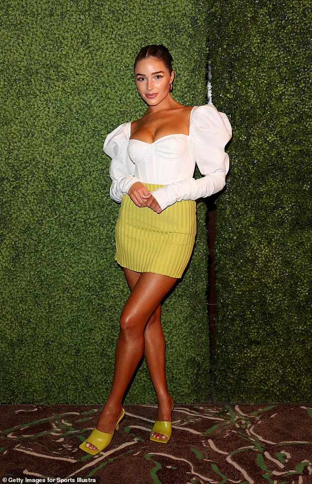 Leggy display:This comes after she rocked a plunging, puff sleeved blouse and lime green miniskirt at a Sports Illustrated party in Florida on July 23