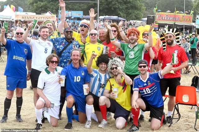 Festival goers pose in football kit, repping Argentina, England, and Italy, on the third day of Latitude festival on Saturday