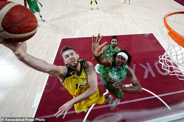 Australia's Nic Kay (15) shoots past Nigeria's Precious Achiuwa (55) during a men's basketball preliminary round game at the 2020 Summer Olympics