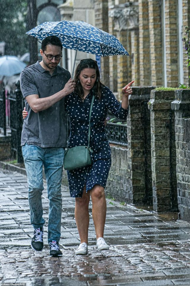 Two people cosy up under an umbrella walking in Wimbledon Village during the heavy rain showers on Sunday afternoon