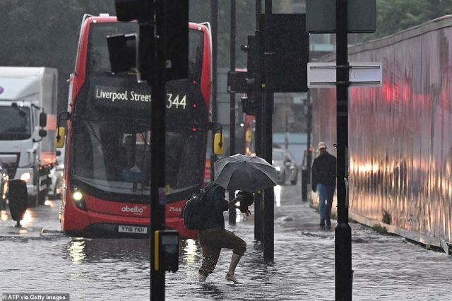 Pictured: A pedestrian crosses through deep water on a flooded road in The Nine Elms district of London during heavy rain