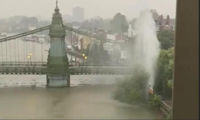 River water levels rose yesterday after downpours. Pictured: A burst water pipe next to Hammersmith Bridge, in West London