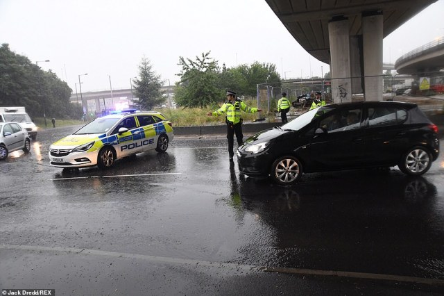 Police officers stop traffic from driving into flood waters and redirect traffic after severe rain caused flooding in east London
