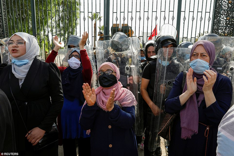 Female supporters of moderate Islamist party Ennahda stand in front of security officers guarding the country's parliament building