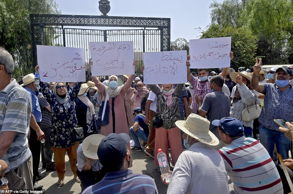 """Tunisian protesters hold up placards with slogans denouncing what they described as a """"coup d'etat"""" outside the parliament building in the capital Tunis"""